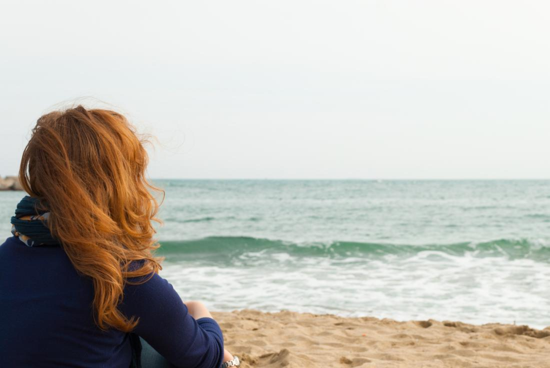 Woman with red hair sat on a beach
