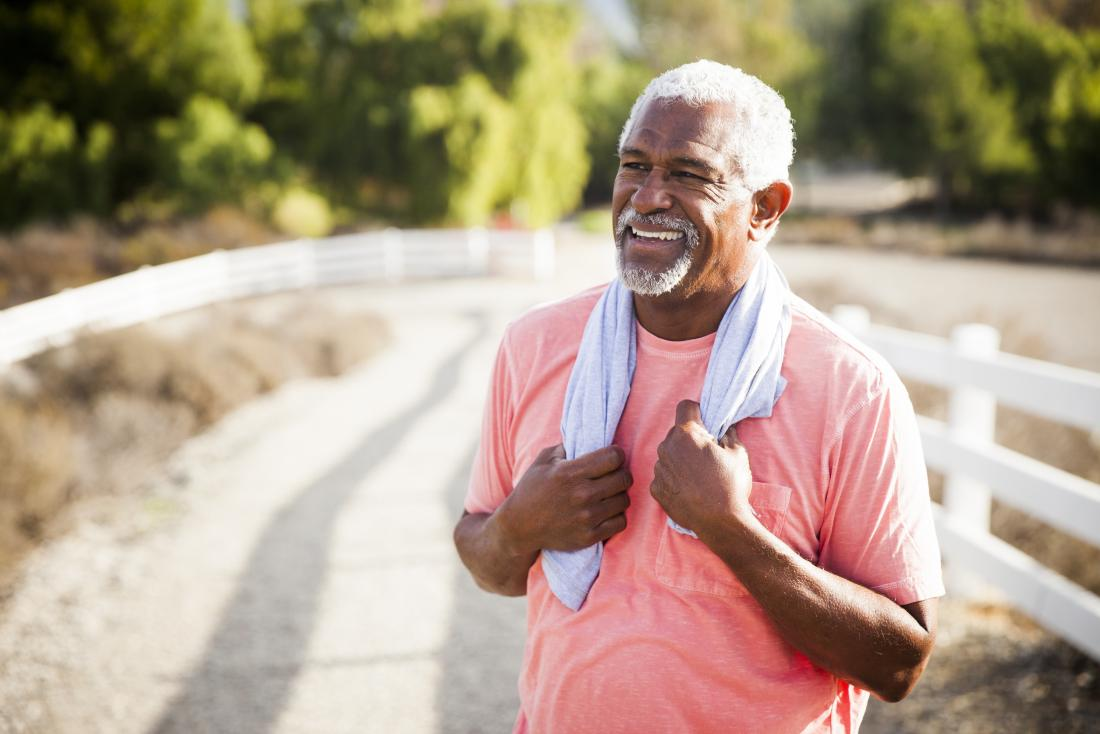 Older man stands outdoors with towel around his neck after exercise