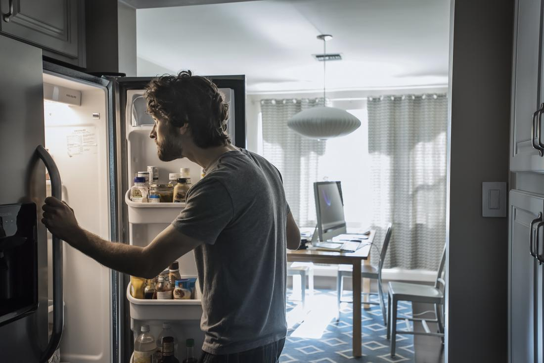 Man working from home looking into fridge