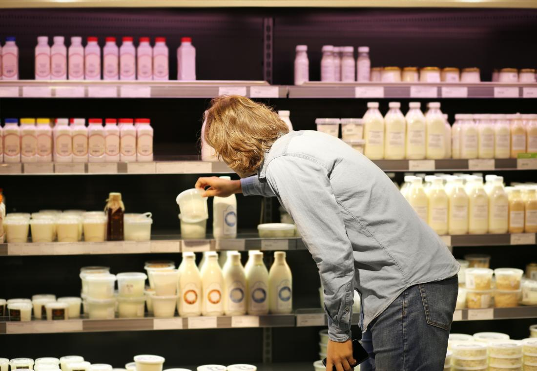 man looking at dairy products in supermarket