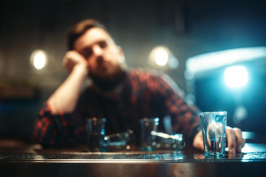 Man drinking shots alone