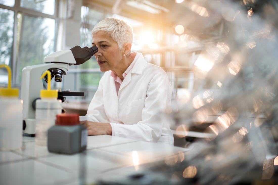 scientist looking at something through microscope