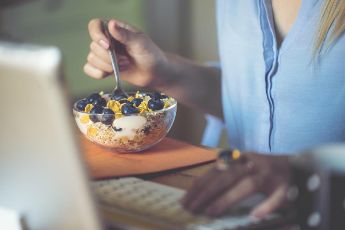 person eating breakfast bowl with blueberries
