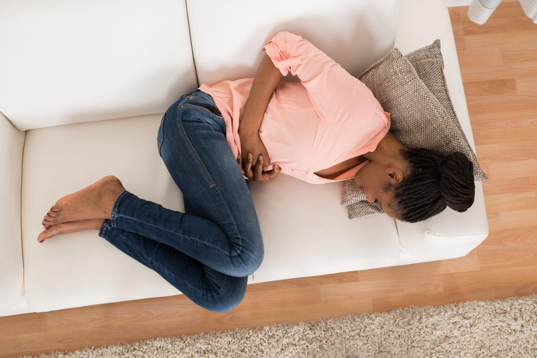 Woman with stomach with cramps on couch