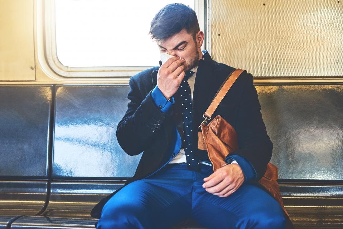 Man sitting on train blowing nose into tissue