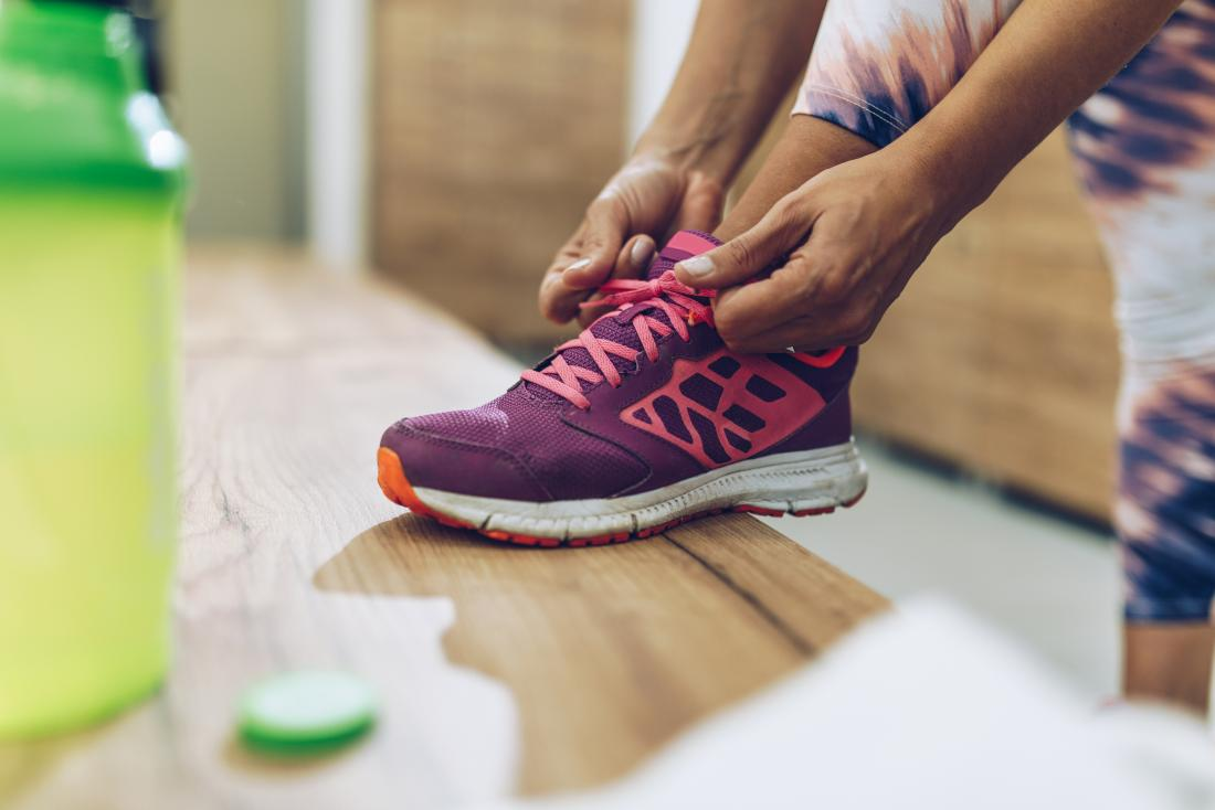 Person tying sport shoes trainers or sneakers in gym dressing room.