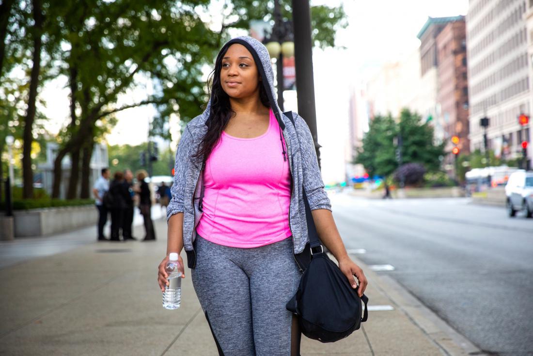 Woman walking through a city in sport gear