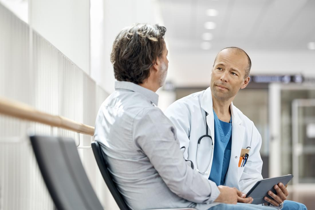 Male doctor speaking to patient in waiting room