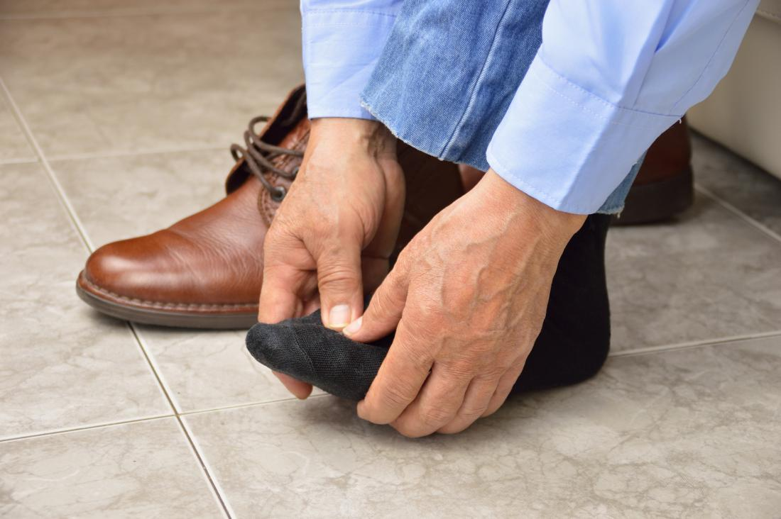 Man pressing top of foot and toes because of pain