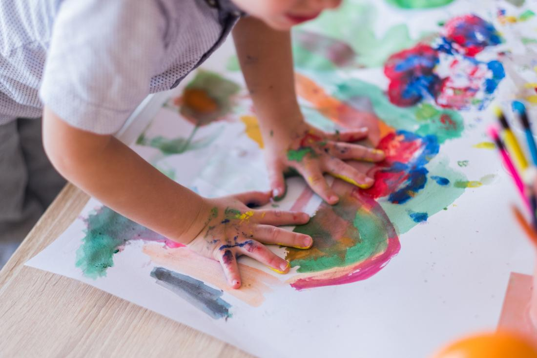 Child with hands on painting