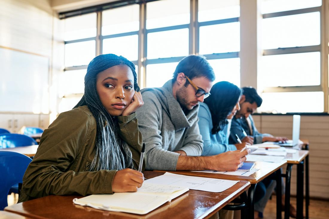 Distracted young woman in lesson or exam looking bored