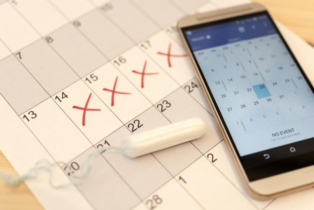 Menstrual cycle being tracked on calendar with period app and tampon.
