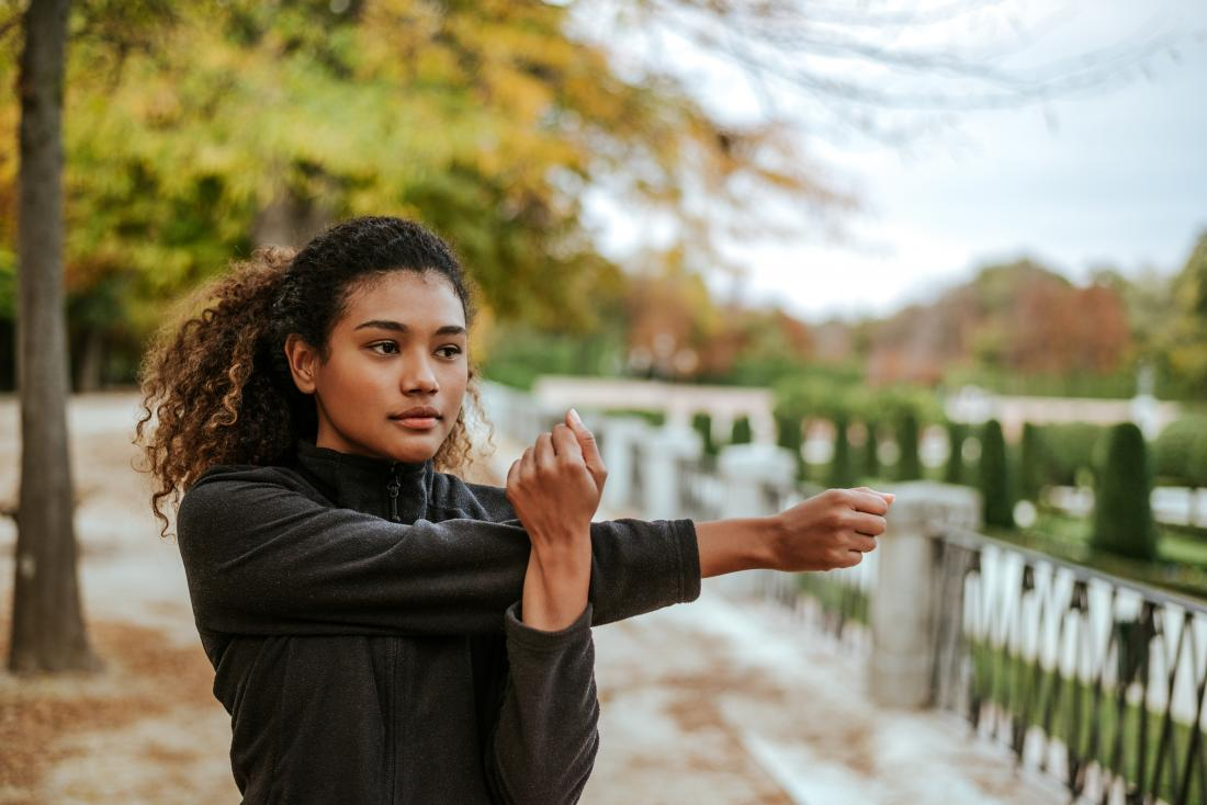 Woman doing Crossover arm stretch outdoors in park.