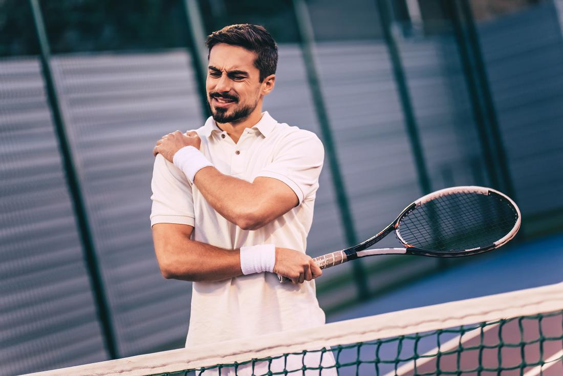 Man playing tennis holding his shoulder in pain because of rotator cuff injury