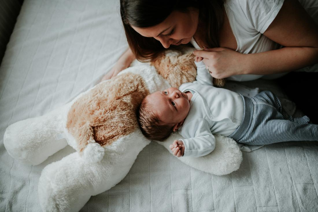 Mother with newborn with blocked tear duct lying on bed