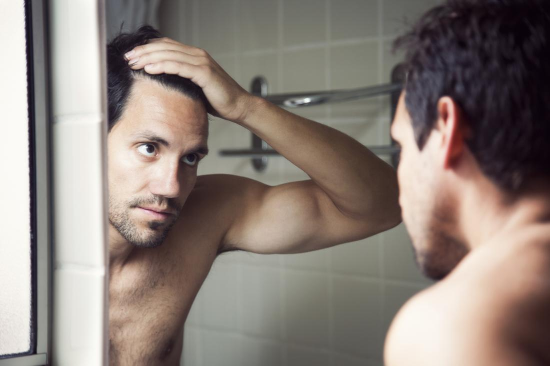 man looking at receding hairline in mirror