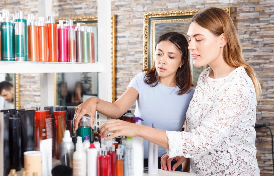 two young women looking at hair products in salon