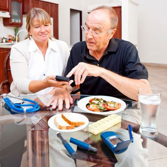A healthcare professional discussing diet and showing a diabetic patient new technology for monitoring blood glucose levels on a smartphone or handheld device.