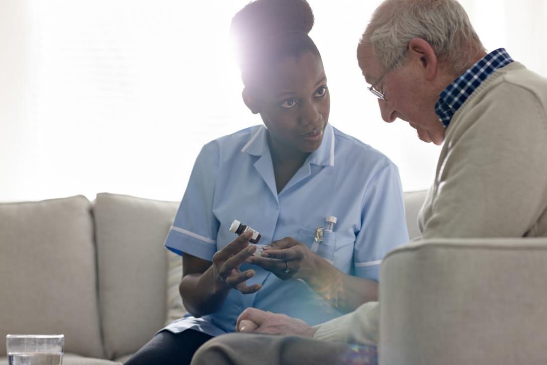 nurse giving senior drugs