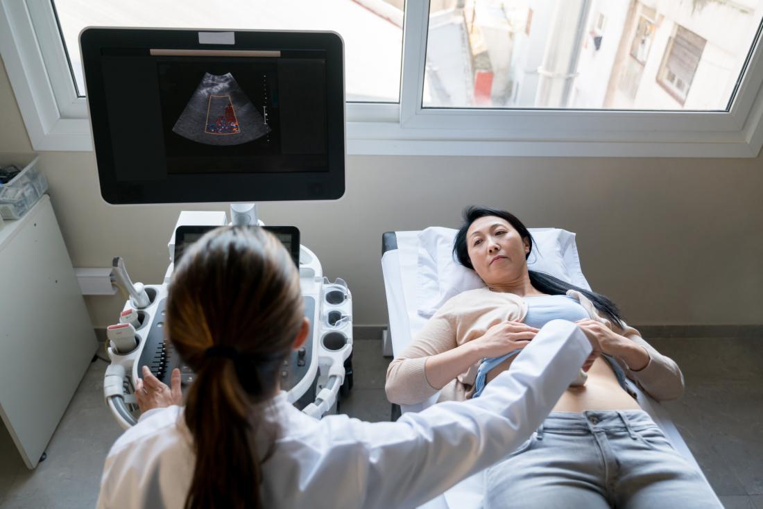 Mature woman receiving ultrasound from technician