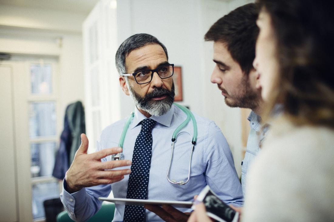 Doctor discussing something with patient couple in office
