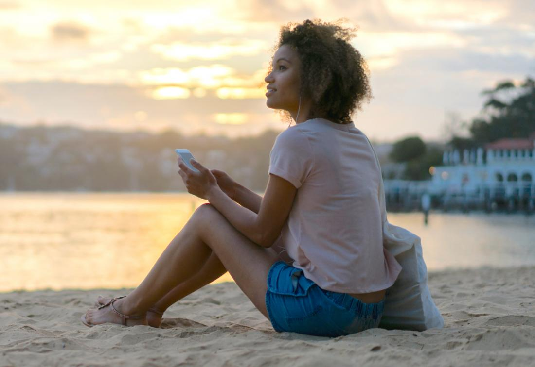 Woman sitting on beach relaxing listening to music to tackle stress and naturally boost fertility