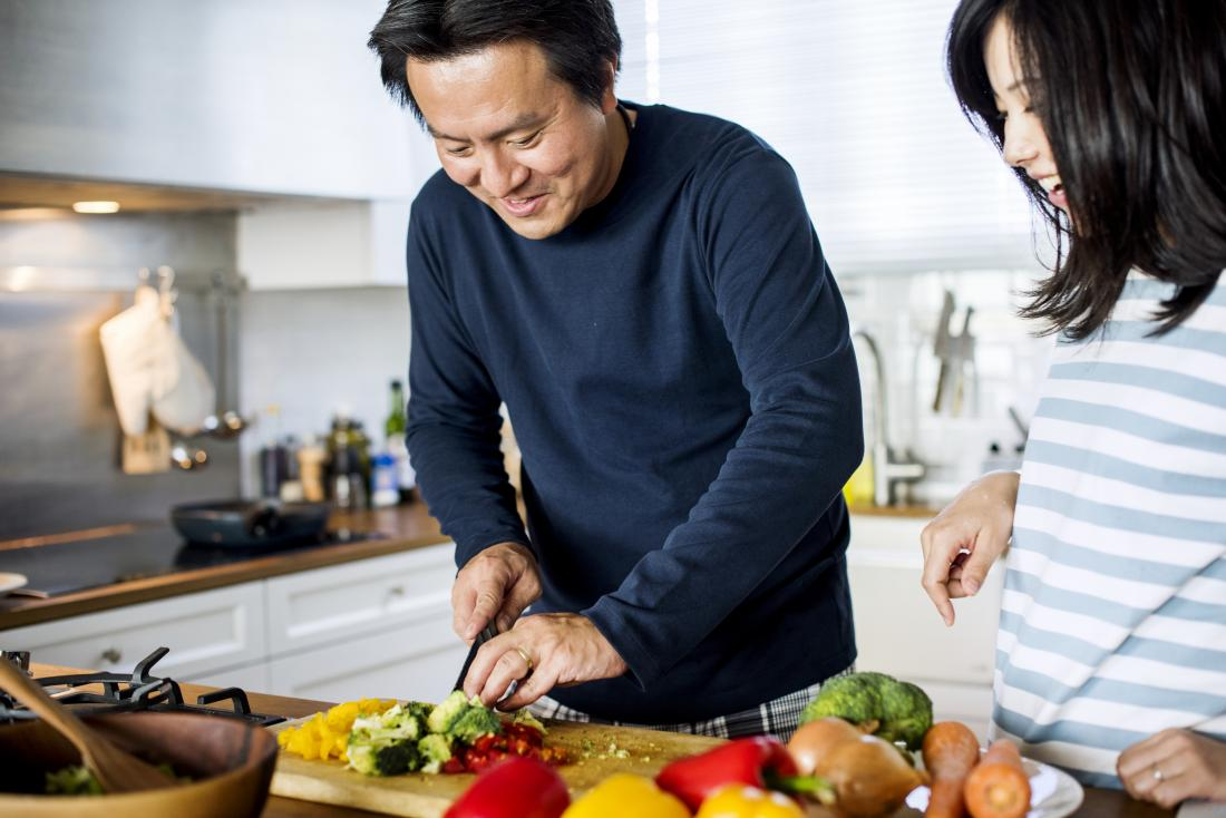 Couple chopping vegetables and cooking in kitchen for paleo diet