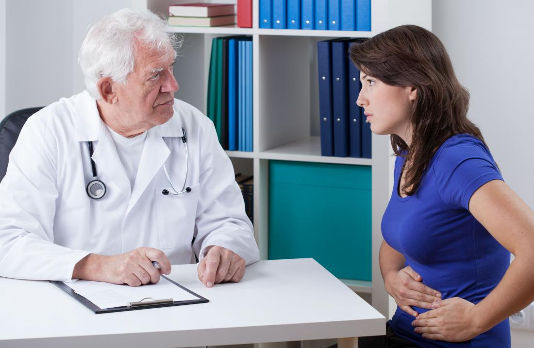 Woman with abdominal stomach pain speaking to doctor.
