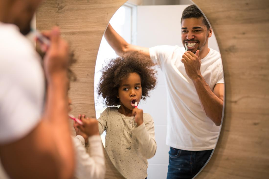 Father and son brushing their teeth in the mirror to remove plaque