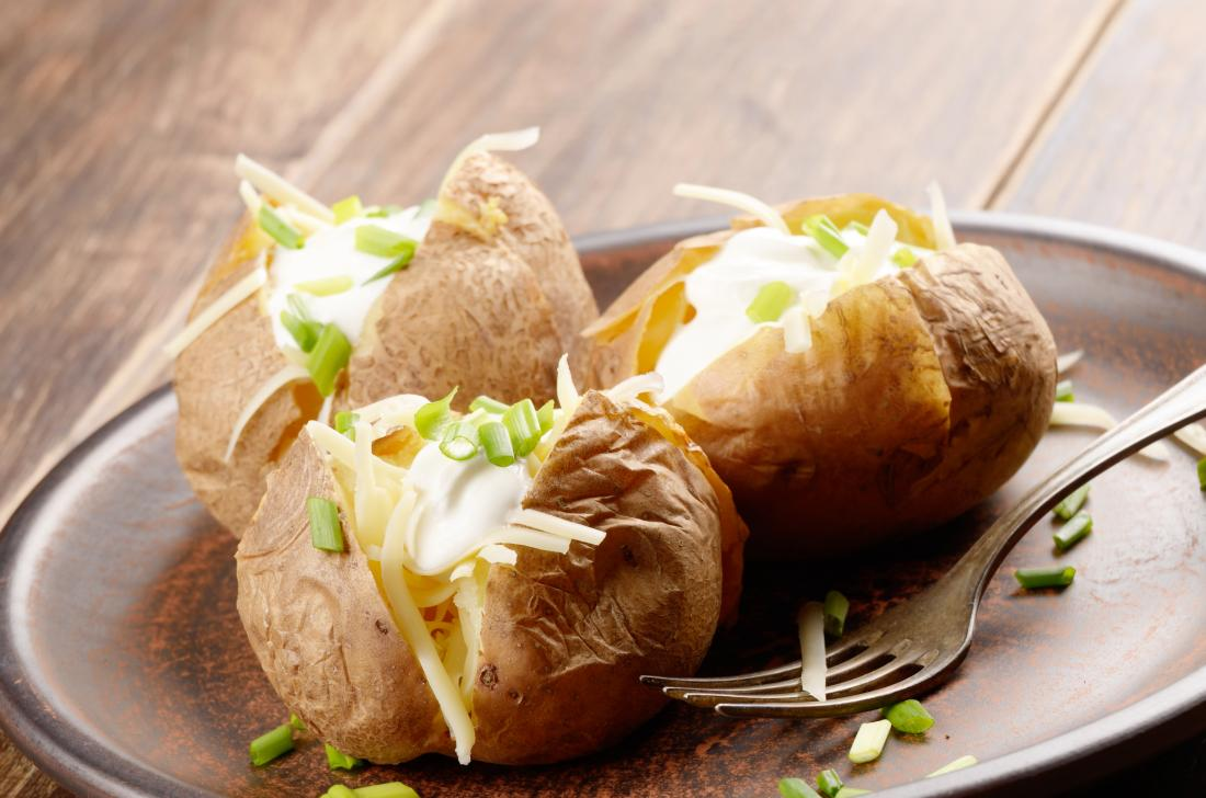 Baked potatoes on plate with chive, sour cream, and cheese filling