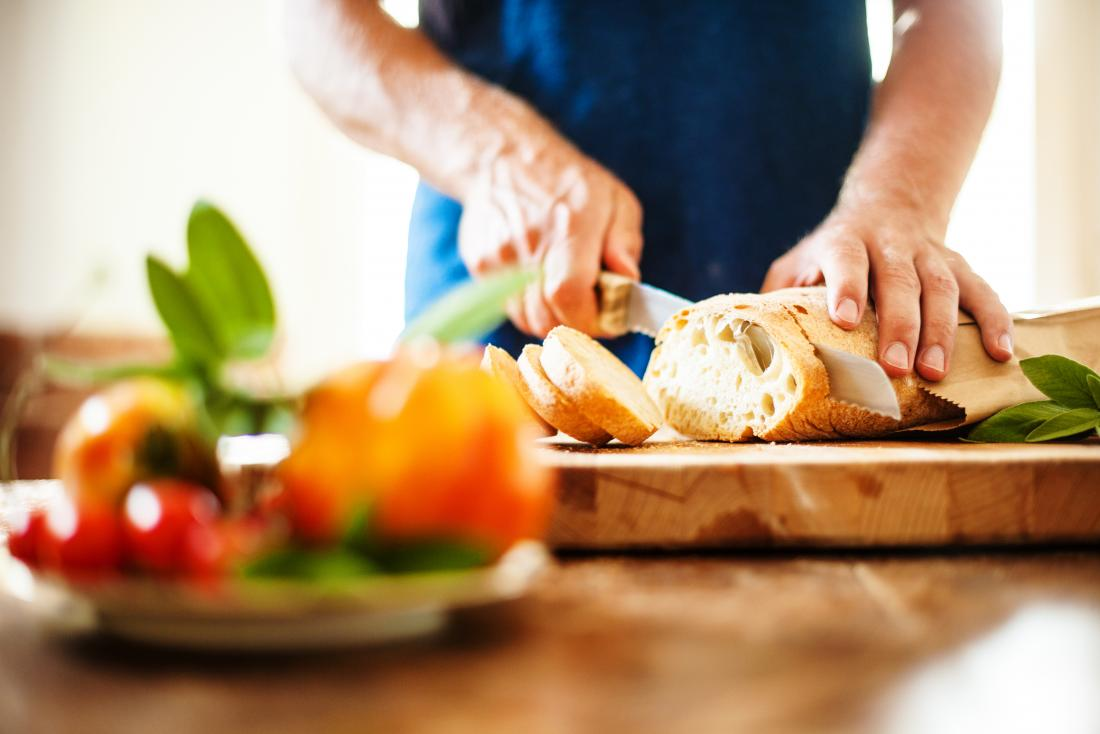 man slicing white loaf of bread