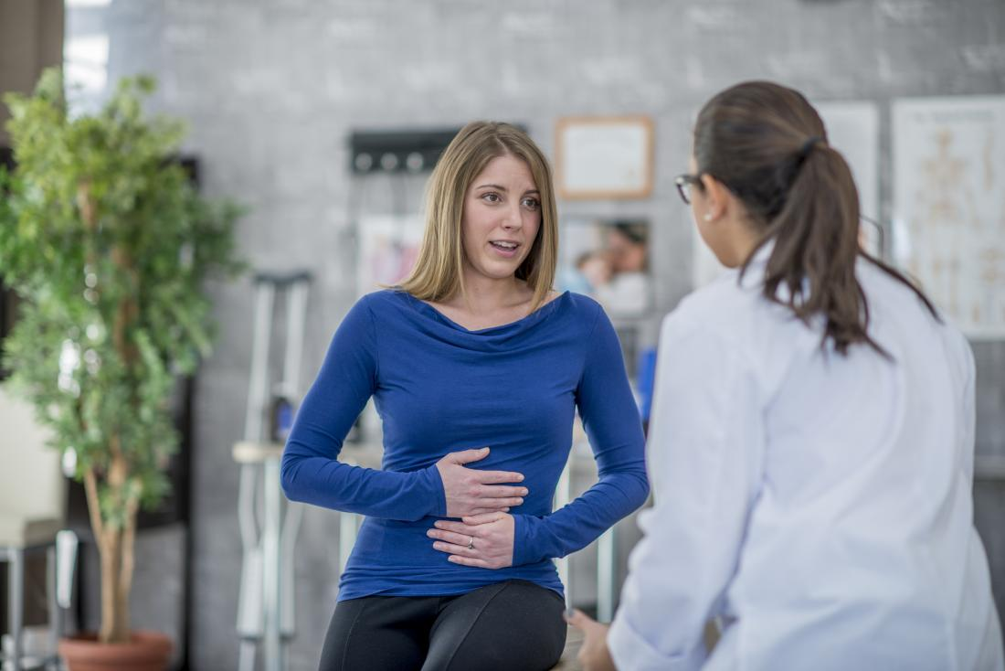 Woman explaining abdominal pain in gynecology office to female doctor.