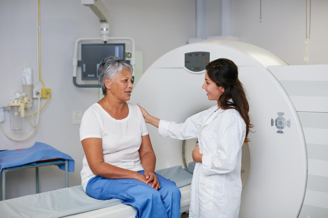 Mature woman sitting on CT scan machine about to have image test.