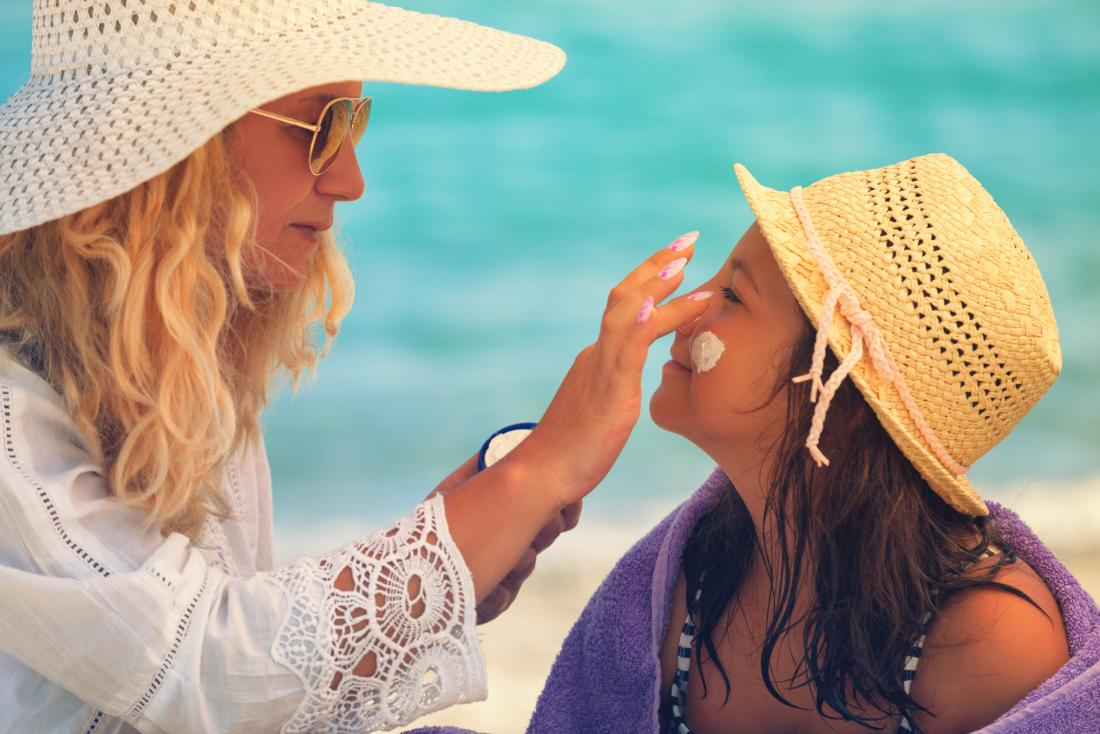Woman in hat and shades applying sunscreen to girls face while sitting on beach in shade for sun protection