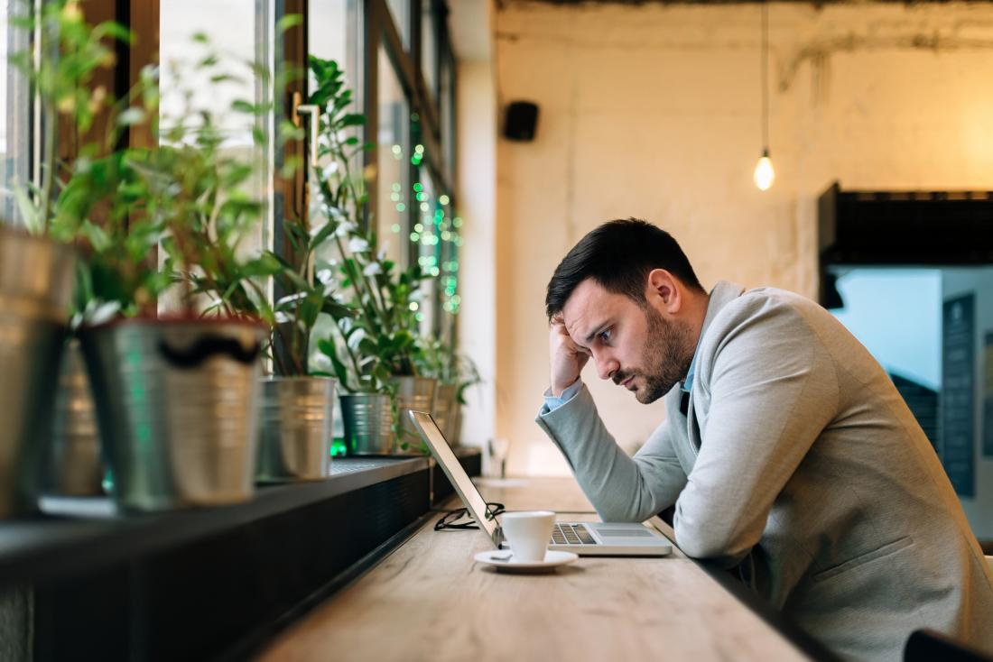 Stressed and worried man looking at laptop screen in cafe