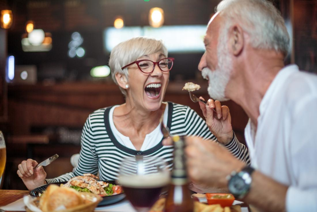Older adults laughing and eating
