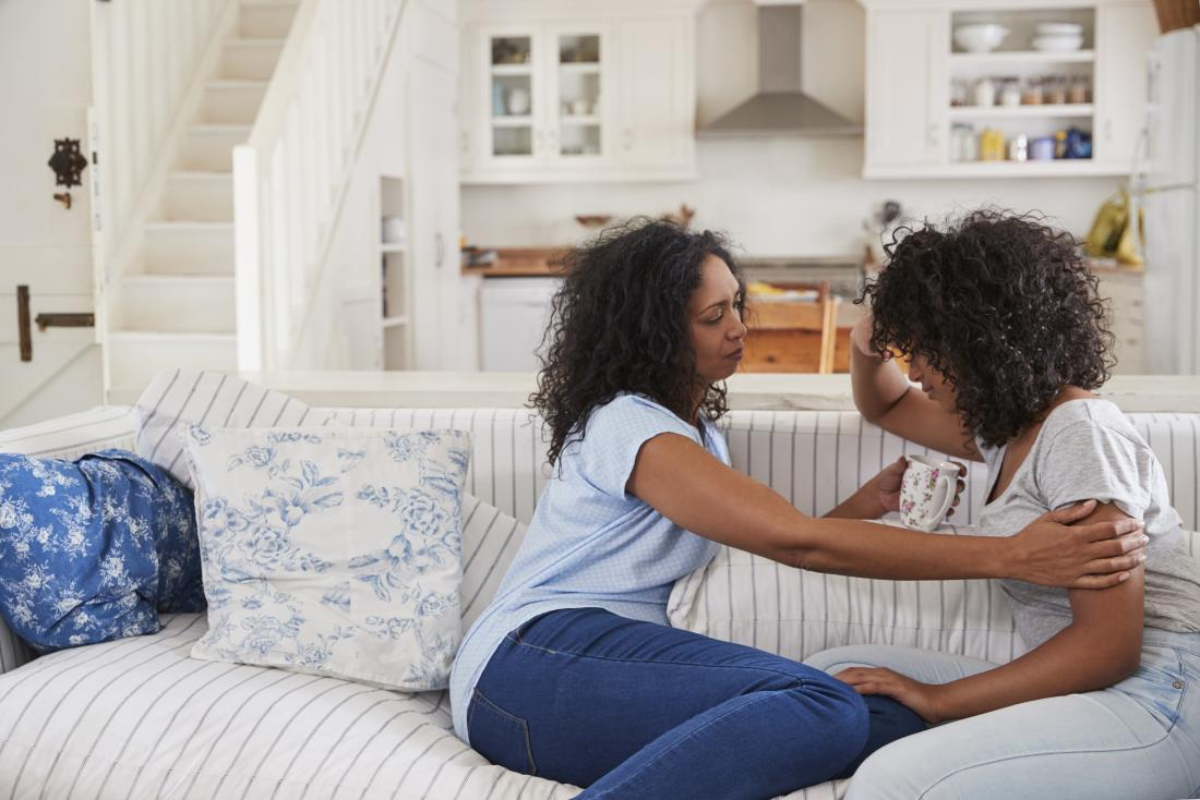 Family sitting on sofa in house comforting each other
