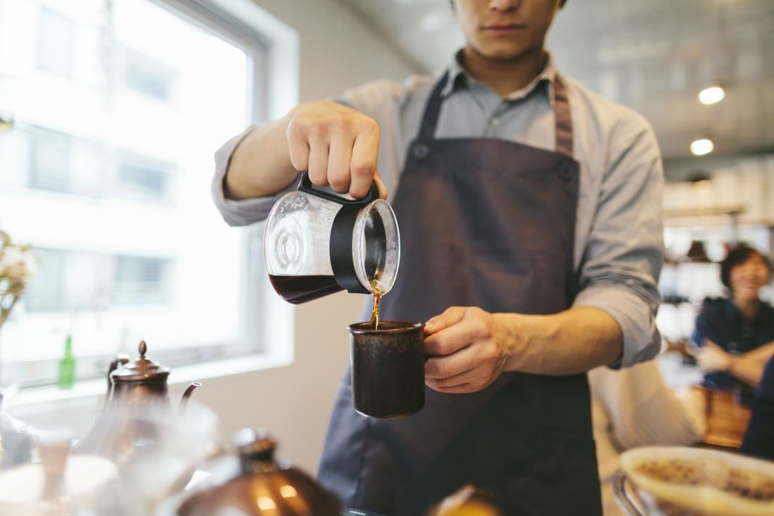 Barista pouring caffeinated coffee into mug in cafe