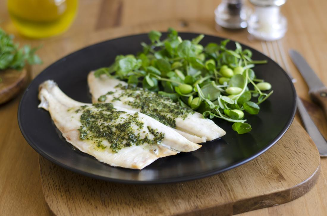 White fish steaks with greens, sprouts and beans on plate