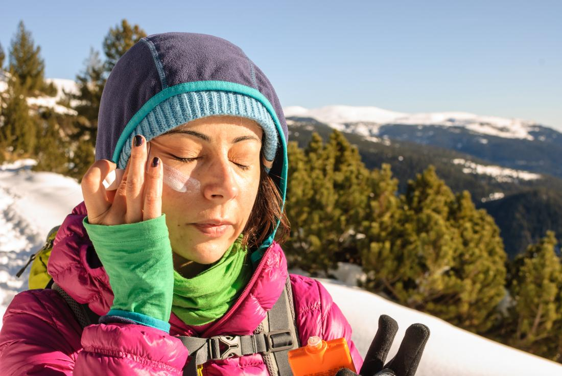putting sun screen on the face on a mountain