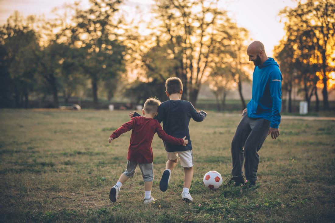 Kids playing football with their dad in a park