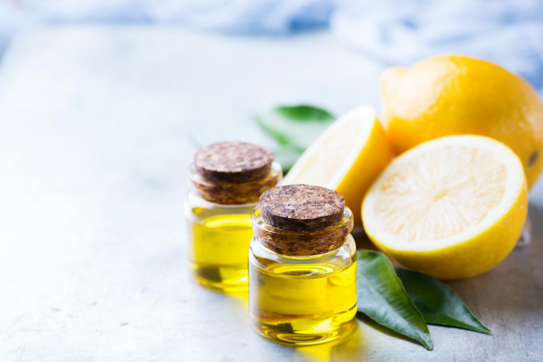 Lemon essential oil in glass jars next to cut up lemon