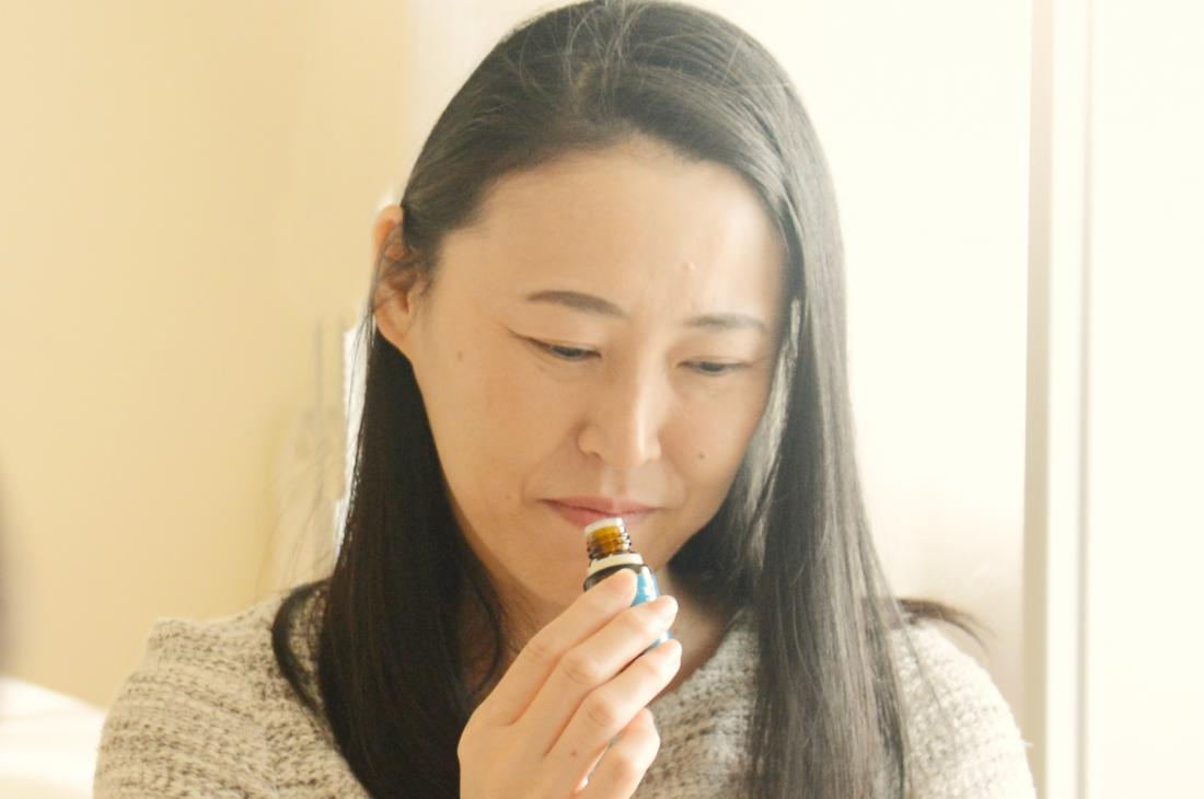 Woman smelling essential oil to ease anxiety