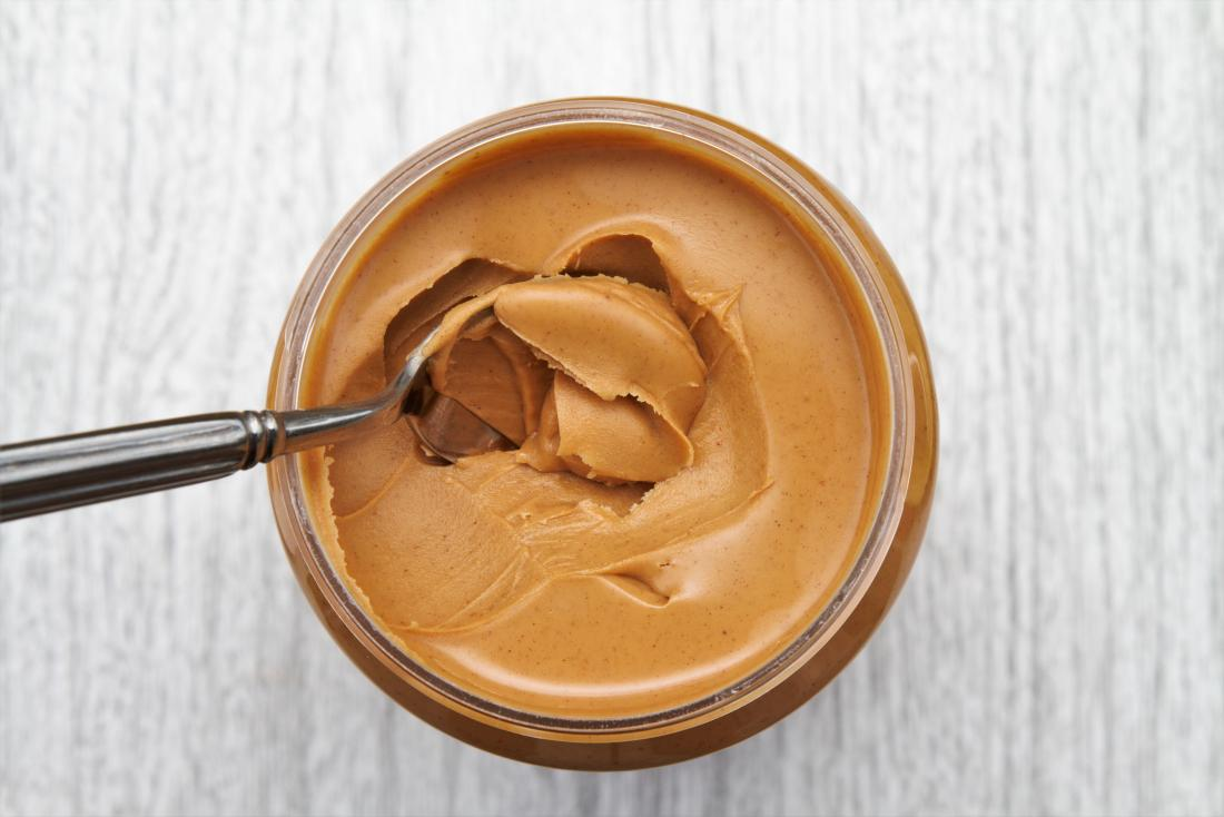 Top down view of spoon in peanut butter jar