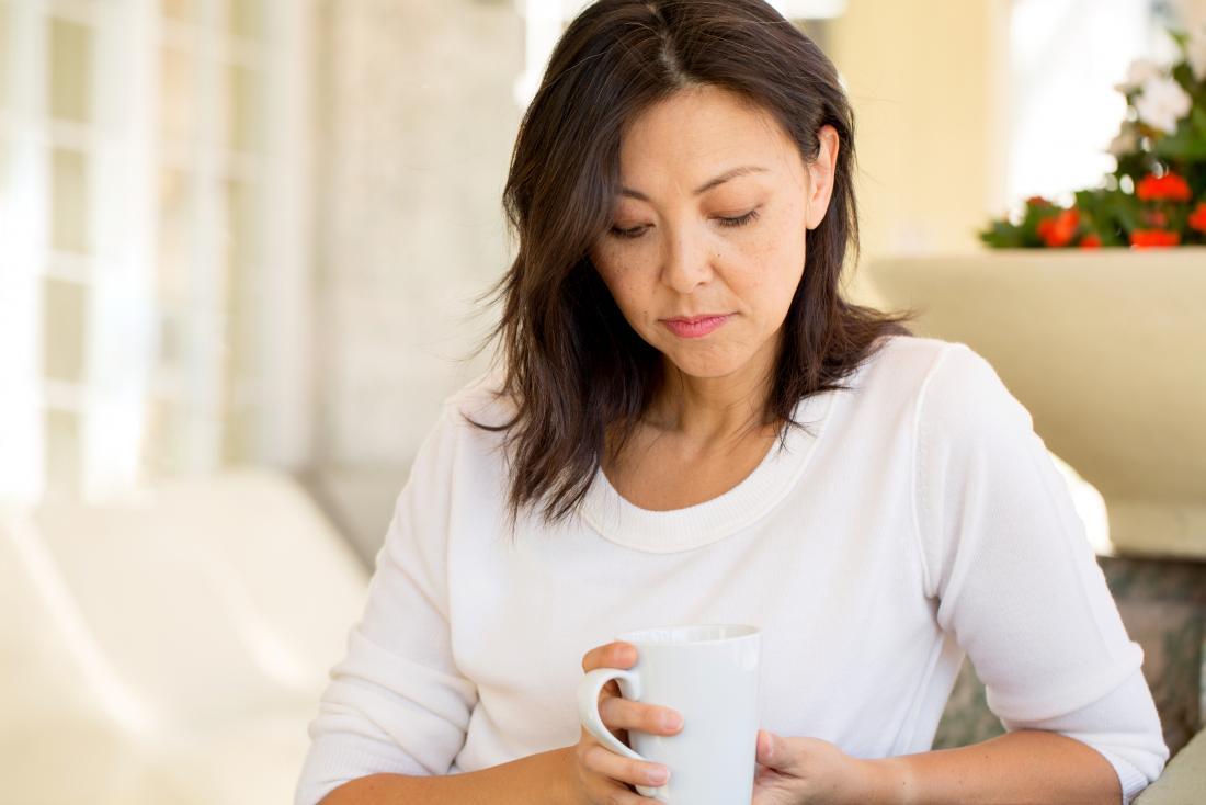 Perimenopausal woman sitting looking into mug of tea.
