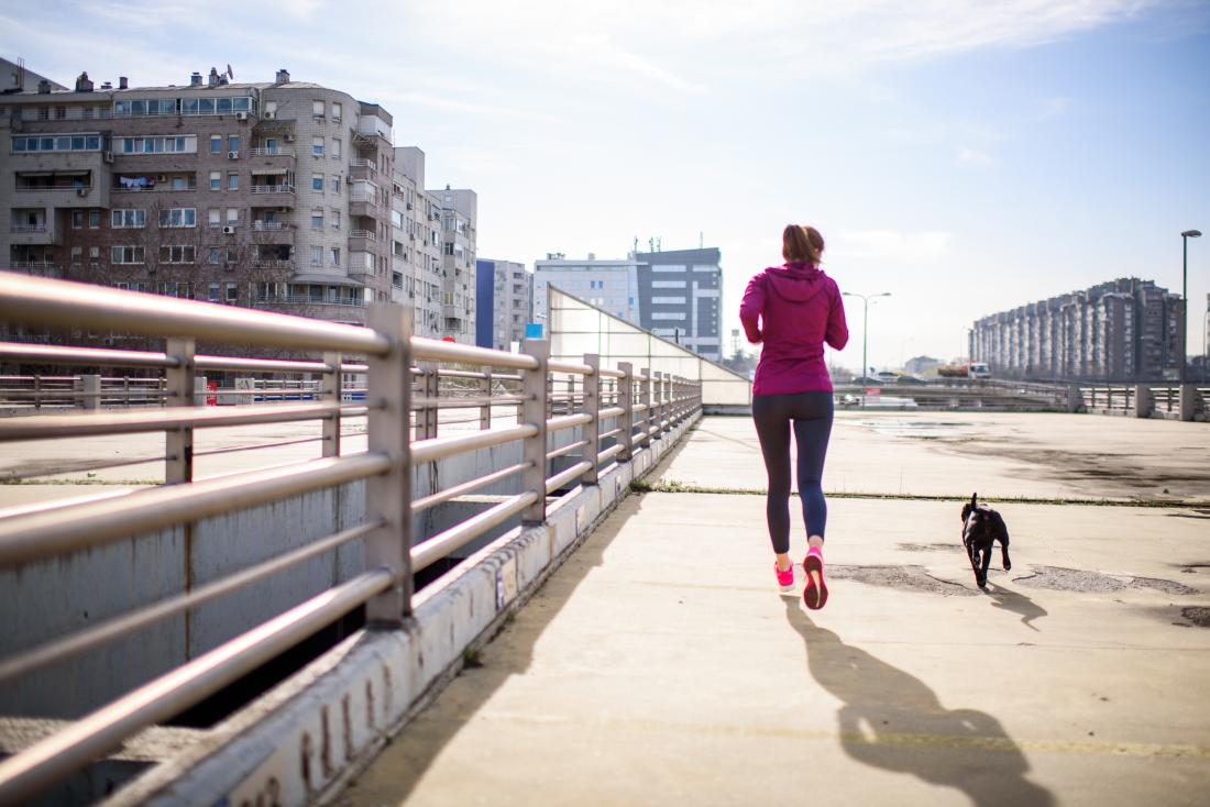 Woman running with her dog which may help get a flat stomach
