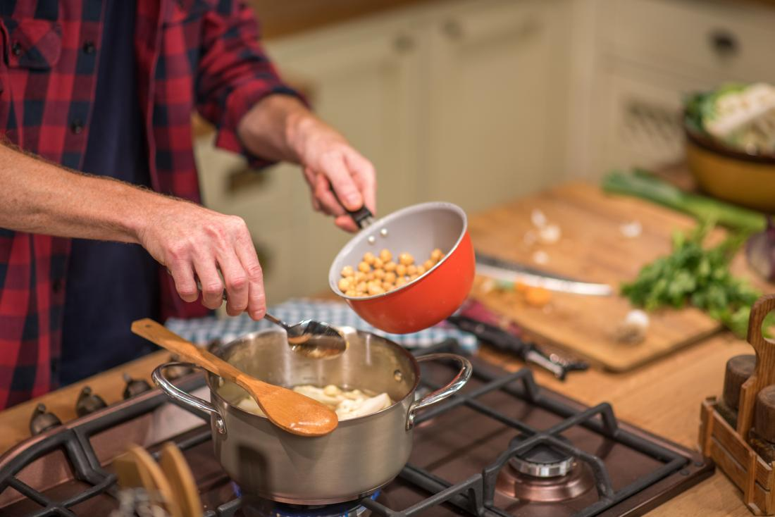 man adding chickpeas to saucepan