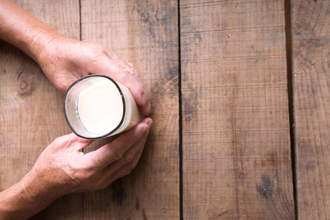 man holding glass of milk on table which may be soy or almond