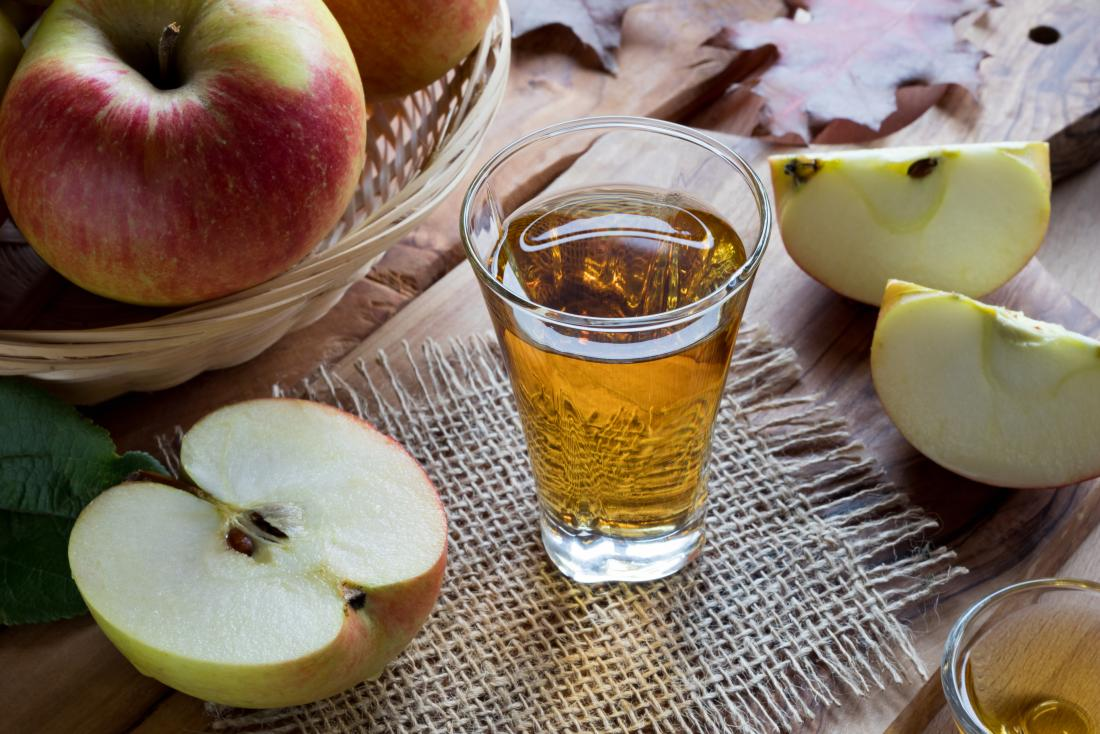 Apple cider vinegar in glass next to bowl of apples and apple slices