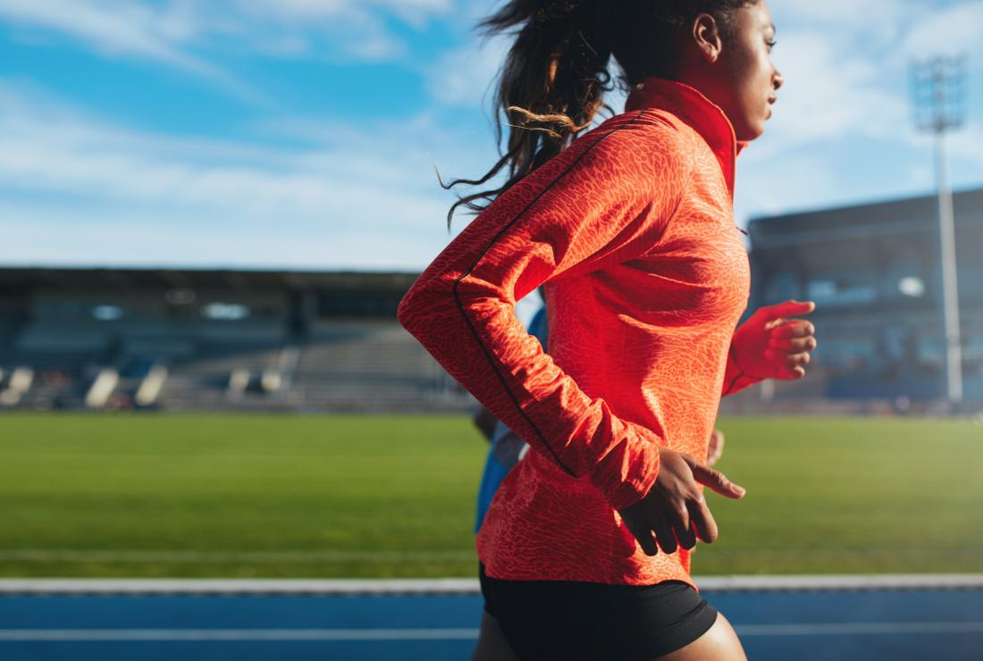 woman using bcaas supplement running on racing track